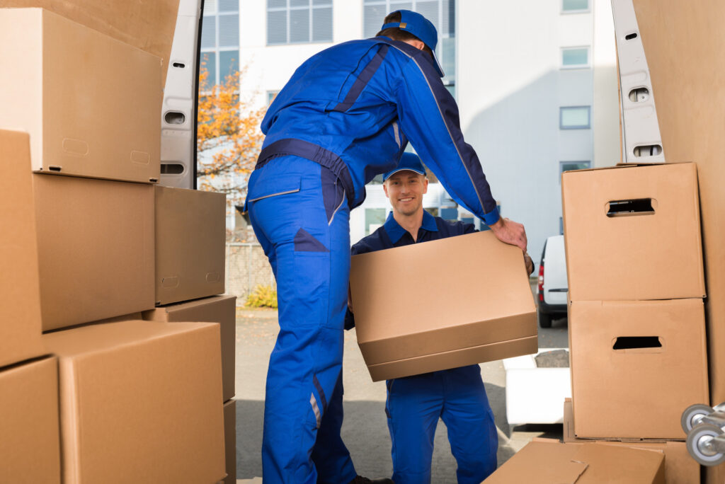 professional movers moving packed boxes off of their moving truck